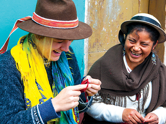 Traveller knitting and laughing with a local Ecuadorian woman
