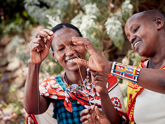 Two Maasai mamas examine beads on a string together in Kenya