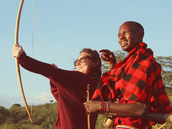 Maasai Warrior teaching traveller to shoot with bow and arrow