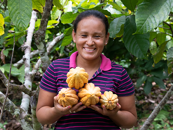 Local woman smiling and holding cacao fruit in the rainforest