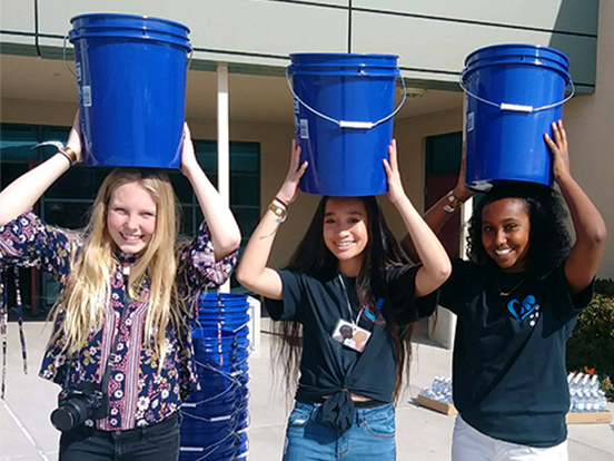 WE Schools students carrying buckets on their heads for a WE Schools campaign