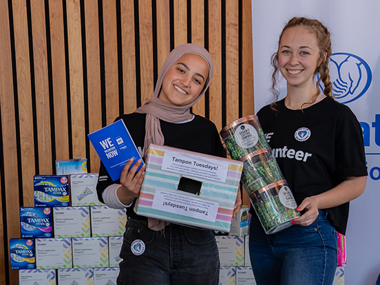 Two girls volunteering, collecting feminine-hygiene supplies as part of a WE Volunteer Now campaign