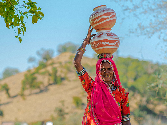Local community member carrying a traditional water pot.