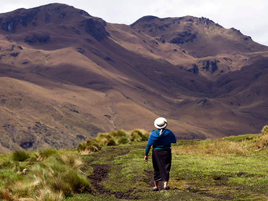 Local woman walking across mountainous field in Ecuador
