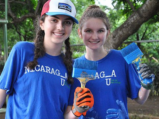 Two Xavieir students hold paintbrushes in Nicaragua.