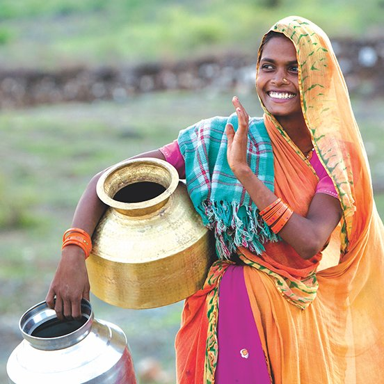 Young local Indian girl in traditional clothing carrying metal water jugs