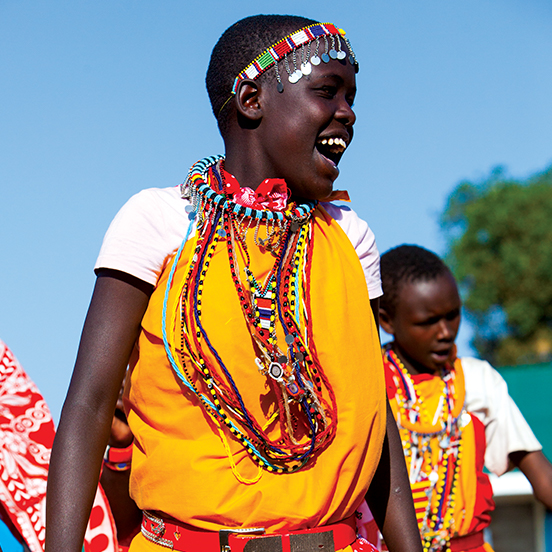 Local Kenyan community members in traditional clothing dancing