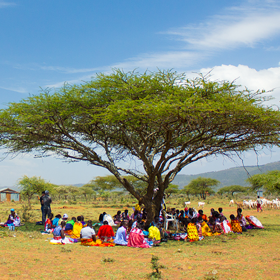 Local Kenyan artisans working together under an acacia tree in the savanna