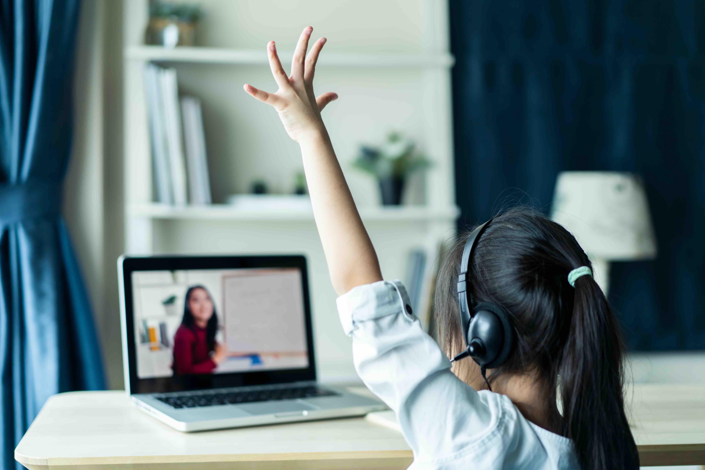 Child on computer, raising hand.