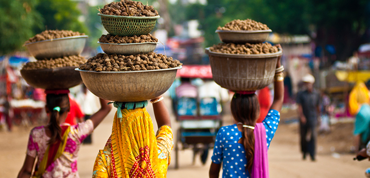 Local women in traditional clothing balancing bowls of food on heads in India walking down street