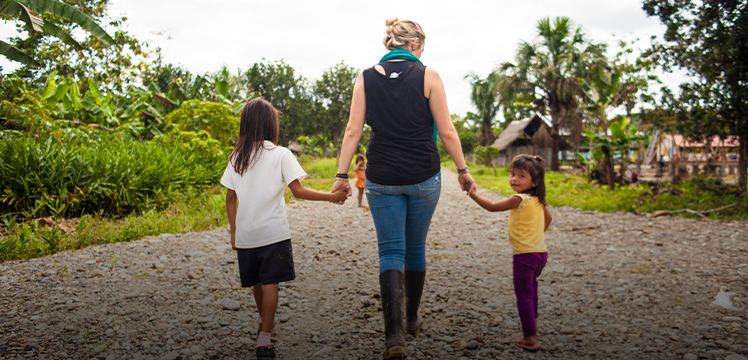 Traveller holding hands and walking with young local Ecuadorian children toward their community
