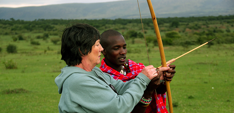 Maasai Warrior teaching traveller how to use a traditional Maasai bow and arrow weapon