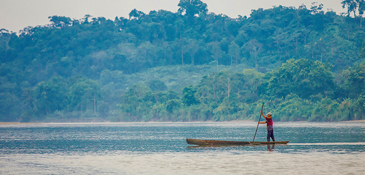 A man in canoe on the Napo River in the Amazon