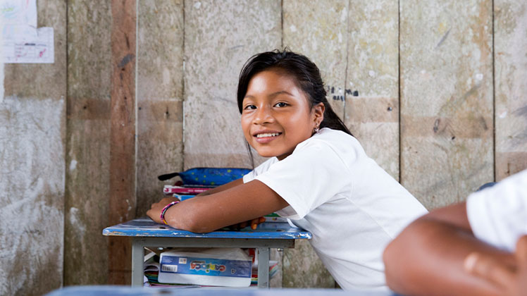 A student sitting at her desk in Ecuador.