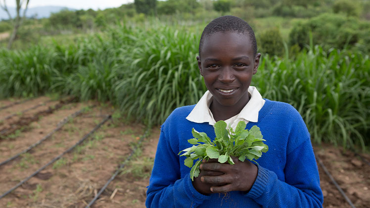 A young student standing in a garden in Kenya, holding a plant and smiling.