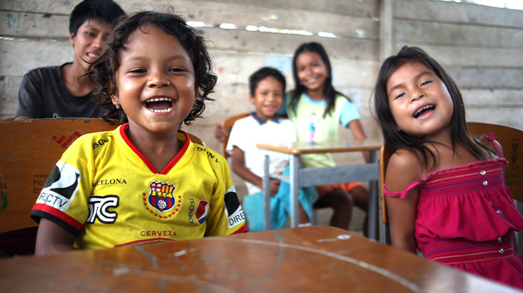 Children sitting in a classroom in Ecuador. They are smiling and laughing.