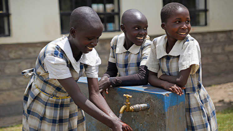 Children washing their hands at a clean water pump in Kenya.