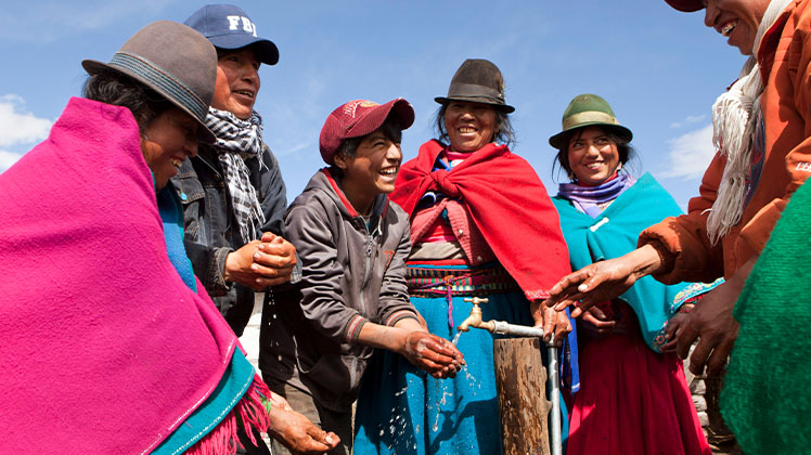 Local community members in Ecuador smile while celebrating a new clean water source.