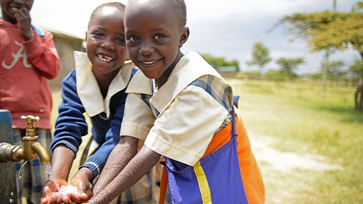 Children in Kenya wash their hands at a clean water pump in Kenya.
